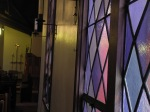 Vintage stained glass suffuses the nave with delicate hues.